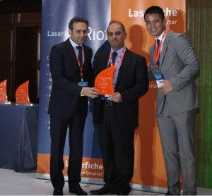 Ghannam (L) and Tang (R) present a Partner Excellence Award to Muath Khatatbeh from Itqan Technologies.
